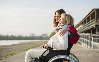 Enkelin umarmt ihre Großmutter im Rollstuhl