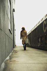 Junge Frau mit Koffer auf Bahnsteig