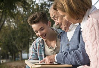 Älterer Mann mit Enkel und Tochter mit Fotoalbum