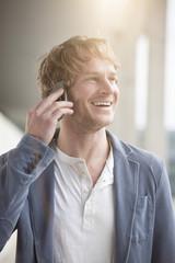 Der lächelnde Mann telefoniert mit Smartphone