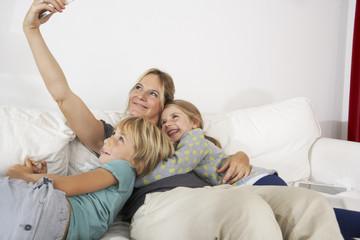 Glückliche Mutter, Tochter und Sohn auf der Couch, Selfie