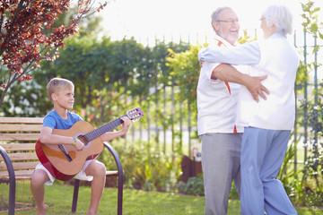Paar tanzt im Park, Enkel beim Gitarre spielen