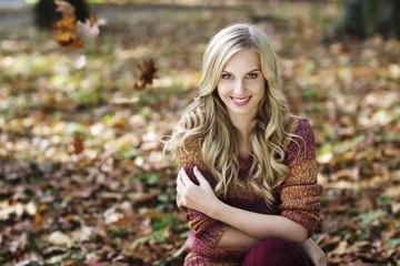 Portrait der lächelnden blonden Frau, trägt Strickpullover, sitzt im herbstlichen Wald