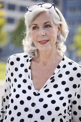 Portrait der lächelnden älteren Frau, trägt weiße Bluse mit schwarzen  Punkten 21d6bf5528