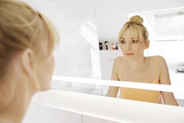 Frau und ihr Spiegelbild im Bad