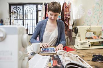 Modedesignerin mit Tablet-PC an ihrem Schreibtisch