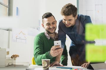 Zwei lächelnde junge Männer im Büro Blick auf Handy