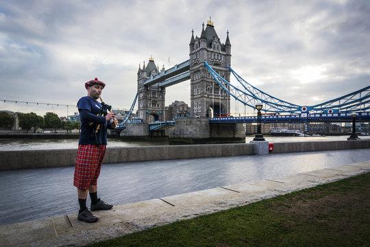 UK, London, Scottish bagpiper at Tower Bridge