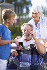 Großmutter und Enkel erklären dem Großvater im Rollstuhl das Handy