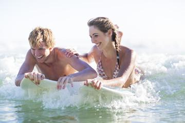 Glückliches junges Paar auf Surfbrettern im Meer