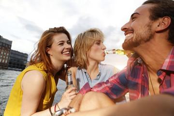 Deutschland, Berlin, Freunde sitzen an der Spree und Bier trinken