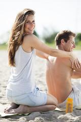Glückliches Paar sitzt am Strand