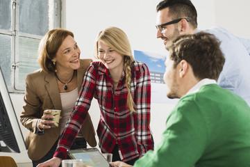 Vier glückliche Geschäftsleute im Büro