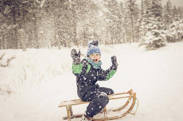 Deutschland, Bayern, Berchtesgadener Land, fröhlicher Junge auf Schlitten