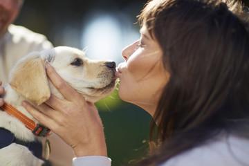 Frau küsst Hundewelpe