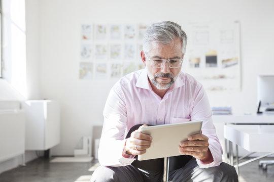 Portrait of businessman using digital tablet in an office