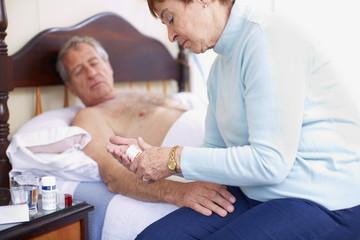 Ältere Frau pflegt kranken Mann zu Hause