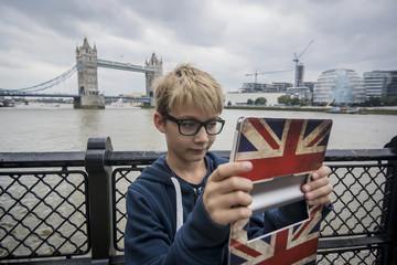 Vereinigtes Königreich, London, Junge macht Foto mit Tablet-PC an der Tower Bridge