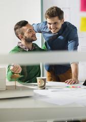 Zwei lächelnde junge Männer im Büro mit Architekturmodell