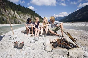 Deutschland, Bayern, Tölzer Land, junge Menschen am Lagerfeuer