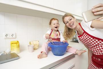 Junge Frau, die ein Selfie mit ihrer kleinen Tochter in der Küche macht