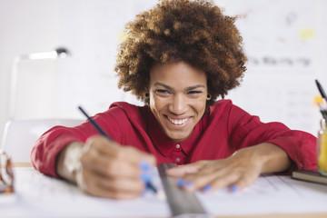 Portrait, lachende junge Architektin arbeitet an ihrem Schreibtisch