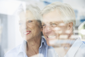 Spanien, Älteres Paar hinter dem Fenster, lächelnd