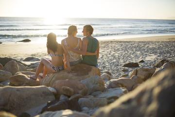 Freunde sitzen am Strand mit Blick auf den Ozean