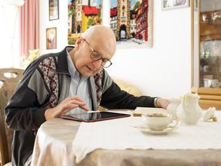 Alter Mann sitzt am Tisch mit Tablet - PC