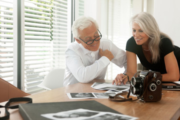Paar schaut auf Fotos die auf dem Tisch liegen