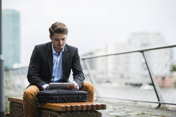 Deutschland, Hessen, Frankfurt am Main, junger Mann sitzt auf einer Bank mit seinem Tablet-PC