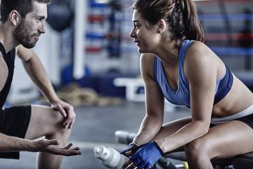 Athlet mit Trainer im Fitness-Studio bei einer Pause