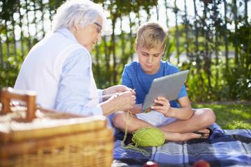 Enkel mit Tablet-PC und Großmutter auf Picknickdecke