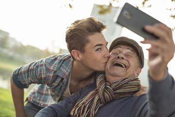 Glücklicher älterer Mann macht ein Selfie mit Enkel