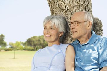 Spanien, Mallorca, älteres Paar sitzt am Baum, Entspannen