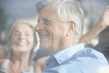 Spanien, Älteres Paar hinter Fenster, lächelnd