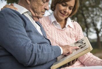Älterer Mann und Tochter mit Fotoalbum