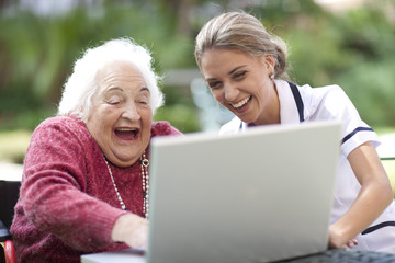 Glückliche Krankenschwester und ältere Frau mit Laptop