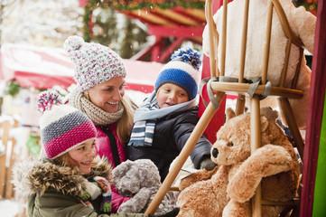 Österreich, Salzburg, Mutter mit Kindern auf Weihnachtsmarkt, lächelnd