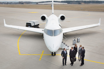executive business team in front of corporate jet talking to pil Wall mural