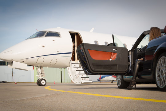 woman convertible car and corporate private jet airplane
