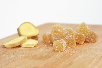 Candied ginger cubes with fresh ginger root on wooden board.