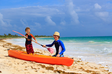 father and son preparing to kayak at the beach