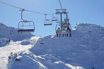 Skiing in mountains, elevated passenger ropeway chairlift