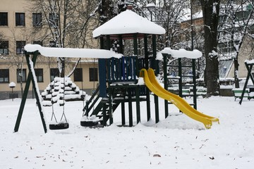 Kids playground in the city covered in snow in winter
