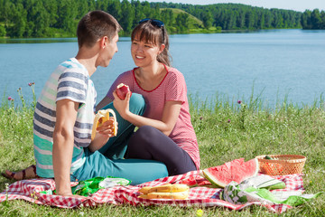 outdoor portrait of happy loving couple having a picnic at the l