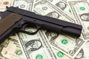 Gun on money background.