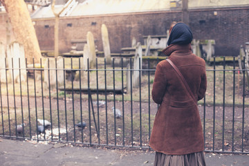 Woman feeding pigeons in cemetery