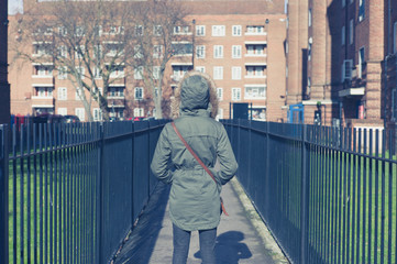Person in warm coat walking on estate