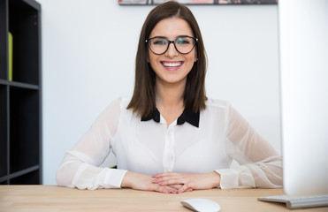 Smiling businesswoman sitting at the table at her workplace